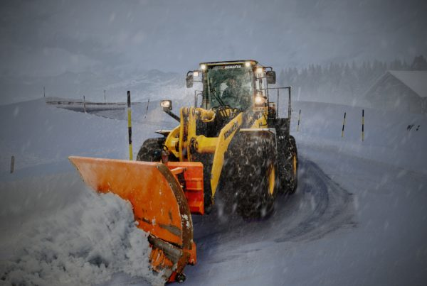 """a snow plow in Calgary performing snow removal"""